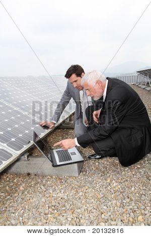 Businessmen checking solar panels running