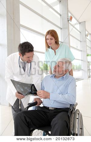 Medical team checking X-ray with patient