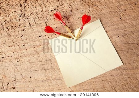 Three darts in an empty or blank notepad on a vintage wooden board