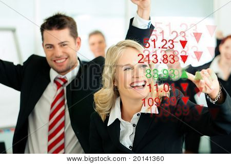 Business - presentation within a team; a female banker or consultant shows figures or share prices on screen