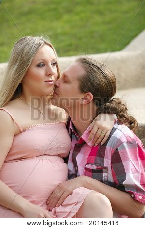Portrait of a happy young man kisses his pregnant wife . outdoor .