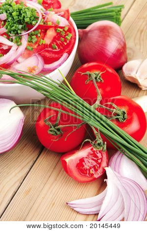 healthy appetizer : fresh tomato salad in white bowl with bunch of chives and raw tomatoes on twig , violet onion, garlic over wooden table