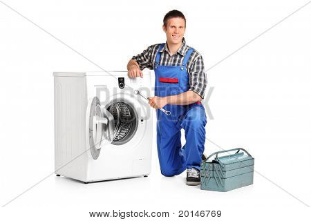 A repairman holding a spanner and posing next to a washing machine isolated on white background