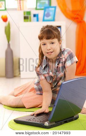 Porträt von kleinen Mädchen mit Laptop zu Hause, Blick in die Kamera.?