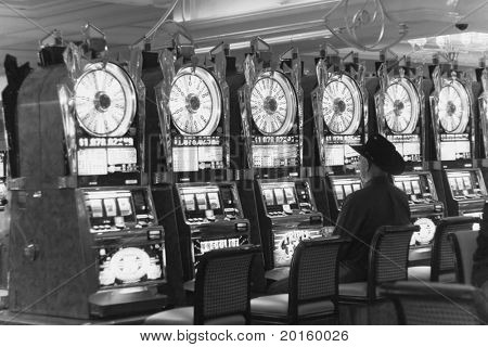 lone cowboy in black sitting at empty row of slot machines lined up