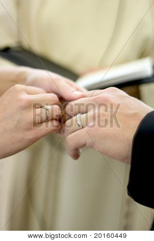 close up of wedding hands with preacher in background