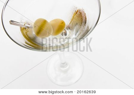 olives in martini glass with wet droplets on glass -  filled with freshly poured martini