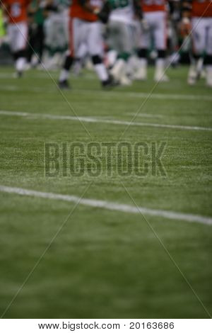 Football field with players at distance, shallow DoF