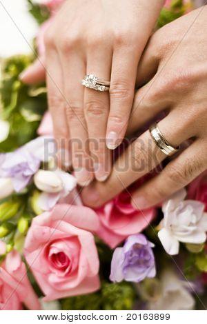 wedding hands over flowers
