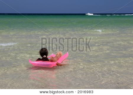 Young Girl On Pink Air-Bed In The Sea