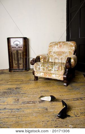 retro scene old fashioned chair radio and a pair of ladies heels strewn about - concept