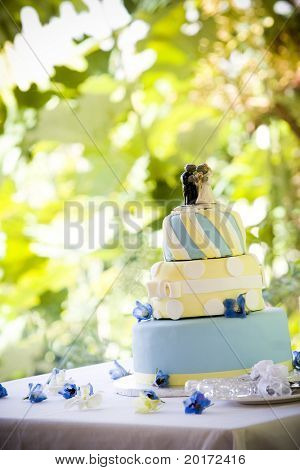decorative wedding cake sitting outside on table leaves behind