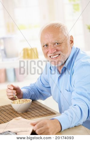 Portrait of healthy older man eating cereal for breakfast, looking at camera, smiling.?