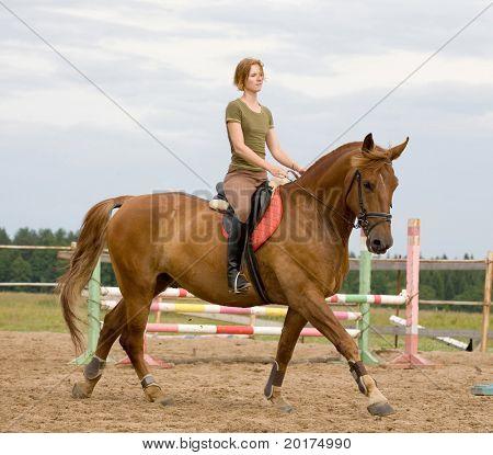 Joven mujer montando a caballo