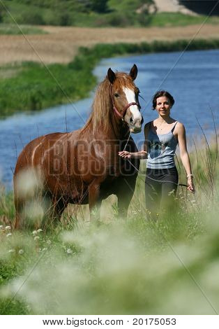 young woman and horse in field near river
