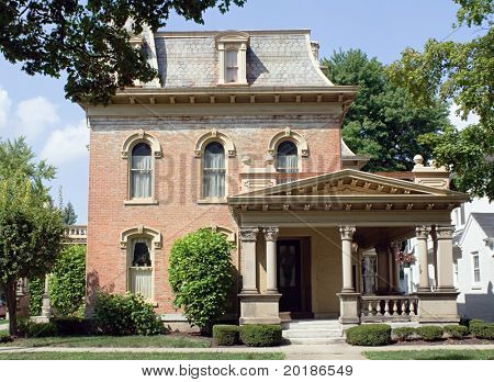 Old Fashioned Brick House with mansard, hipped roof & Corinthian columns.