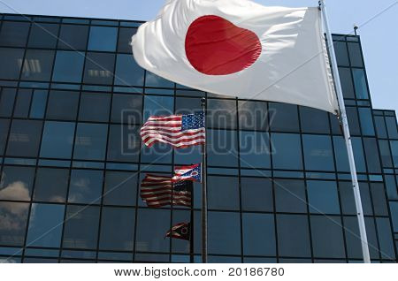 Japan, USA and Ohio Flags in front of glass building.