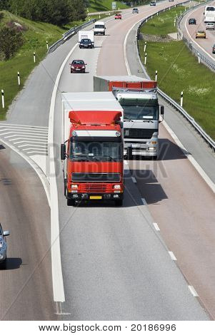 two lorries, trucks, one overtaking the other, surrounded by traffic