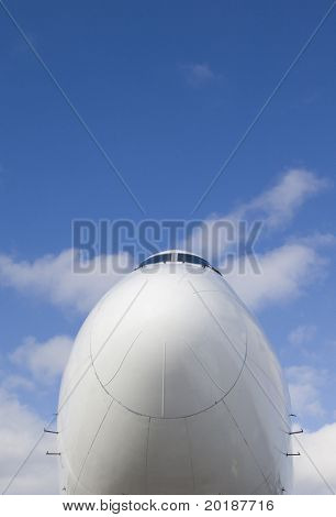the nose of a Jumbo-jet-plane against clouds