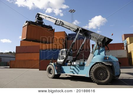 giant forklift-truck stacking containers in commercial port