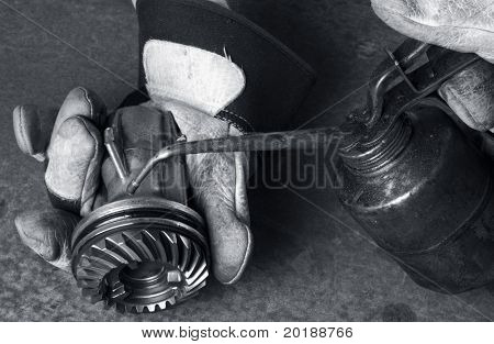 gloves, gear and oil-can lubricating a gear in bluish toning
