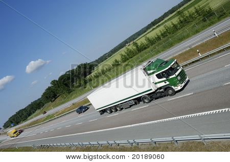 clean green and white truck driving on countryside freeway