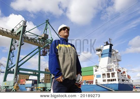 chief engineer standing in front of large commercial-port as background, crane and ship