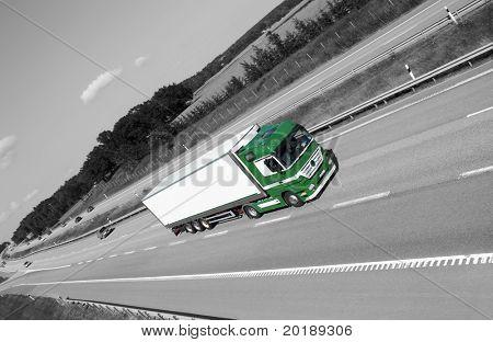 LKW-fahren auf Autobahn mit schwarzen und weißen Land-Seite im Hintergrund