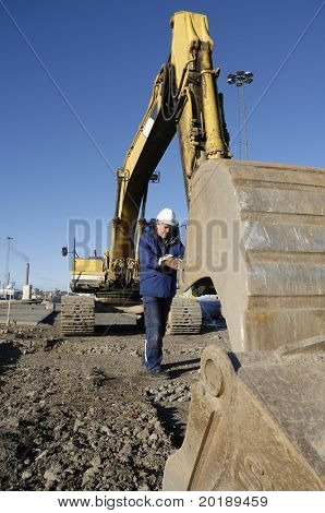 driver inspecting scoop on large digger, bulldozer