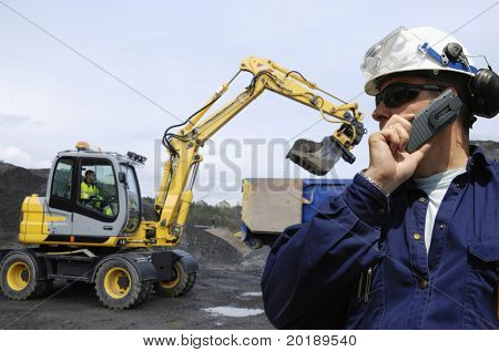 engineer overlooking bulldozer, digger and its driver