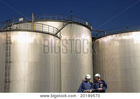 two engineers standing in front of three large refinery storage tanks