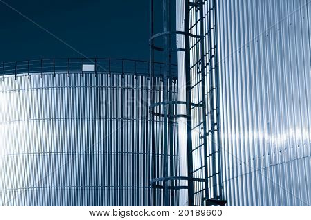 two large refinery oil tanks and in a bluish toning idea