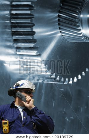 engineer in hard-hat standing in front of large gears, cogwheels, blue toned background