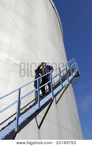 Ingenieur in Bauarbeiterhelm, Kraftstoff-Vorratsbehälter entlang