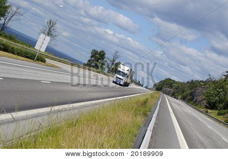 distant truck speeding on scenic highway, very wide and tilted perspective.