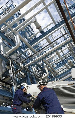 engineers working on giant pipeline pump inside fuel and gas industry, refinery