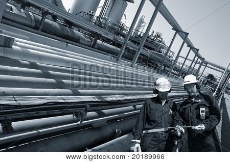 two engineers walking alongside large pipeline construction inside oil-refinery, blue toning idea