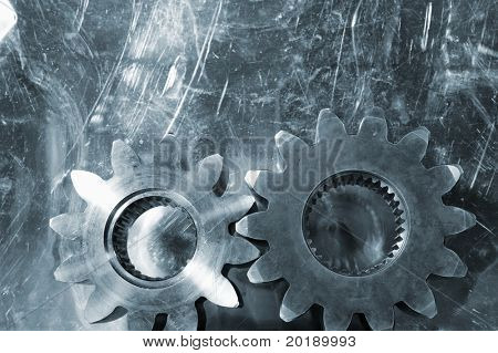 large industrial gears set against scratched aluminum and in metal blue toning