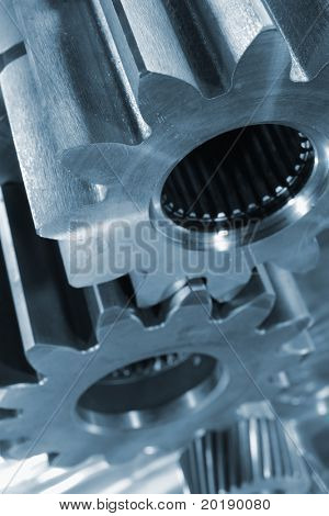 large industrial gears, pinions against brushed aluminum and in a blue toning idea