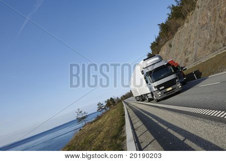 large truck driving on highway with scenic surrounding of sea and mountain-pass