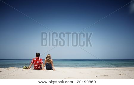 Young man and woman sitting on warm sand at sunny day and looking to somewhere