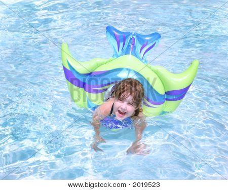 Young Child Playing In A Pool