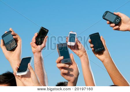 Happy people showing their modern mobile phones against blue sky