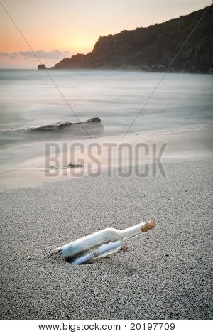 Message in a bottle on a sandy sea shore.