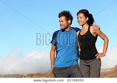 happy couple looking outdoors. Sporty healthy young interracial couple looking at blue sky smiling. Asian woman and Caucasian man on Teide, Tenerife, Spain.