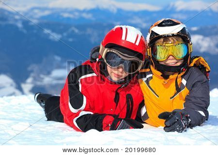 Smiling young boy and girl in ski helmets and goggles on snowy Alpine mountain summit, Winter scene.