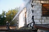 foto of firehose  - Firefighter with firehose spraying water at a fire - JPG