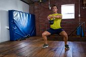 Determined man exercising with kettlebell in fitness studio poster