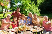 leisure, holidays and people concept - happy family having festive dinner or summer garden party and poster