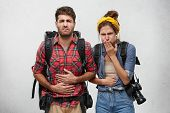 Food Poisoning, Nausea And Sickness Concept. Portrait Of Young Man And Woman Tourists Feeling Stomac poster